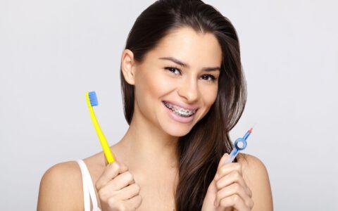 Junge Frau mit Zahnspange und Zahnbürste und Zahnspangenputzer in den Händen