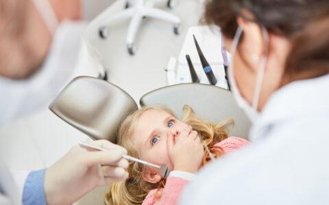 Kleines Mädchen auf dem Zahnarzt Stuhl, welches sich den Mund zu hält und Zwei Ärzte die Instrumente halten