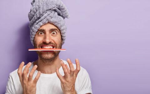 Mann mit einem Handtuch auf dem Kopf und einer Nagelpfeile im Mund